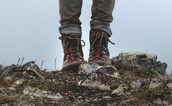 A pair of hiking boots on rocky ground.